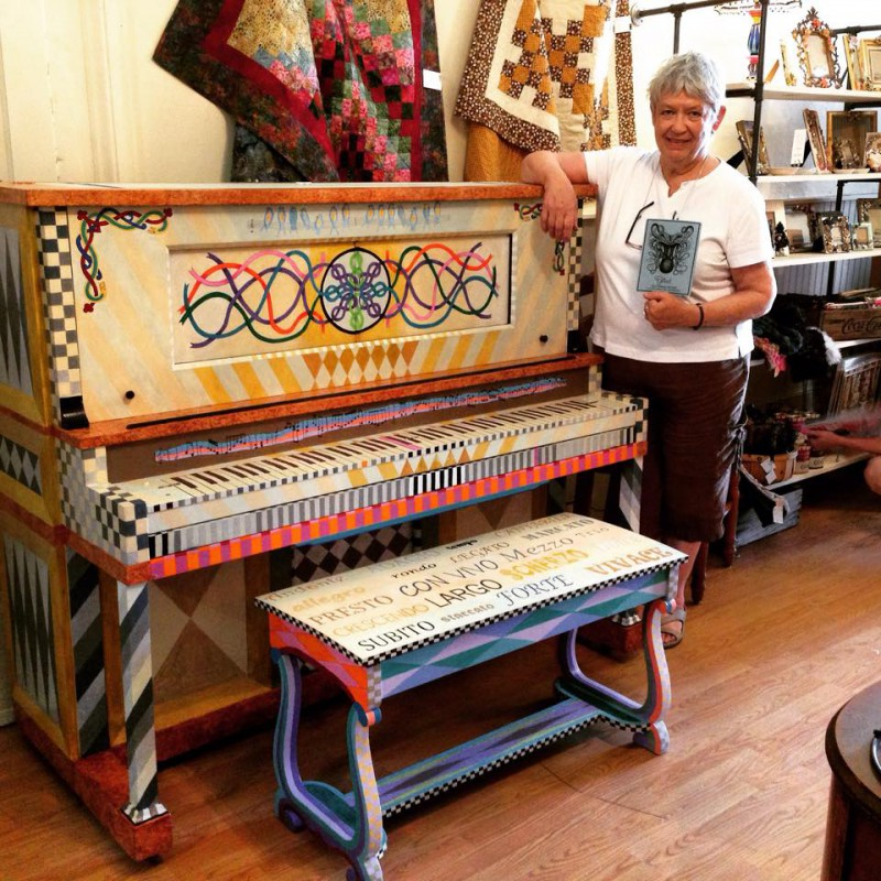 Artist Charleen Tyson stands with her finished work on the Painting the Piano Project.